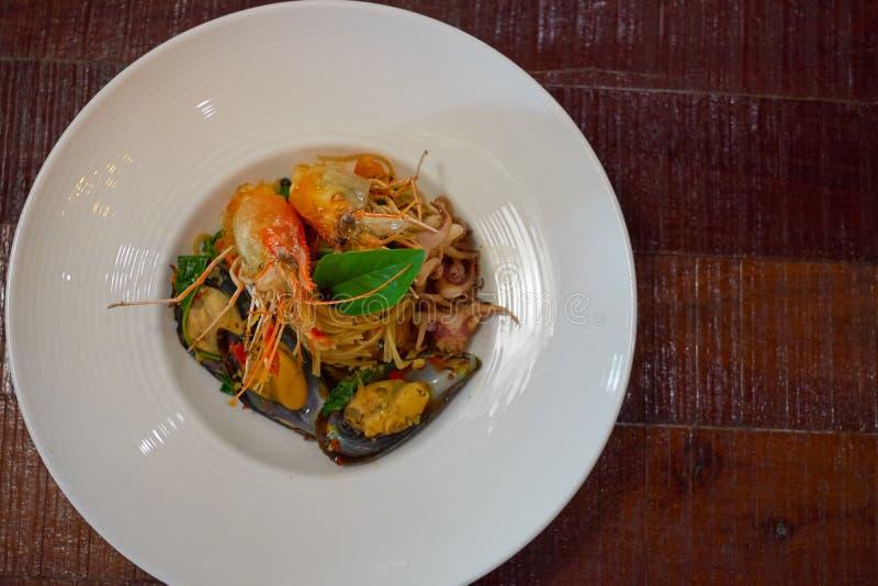 Les spaghetti ?pic?s de fruits de mer remuent la protection frite Cha ont roul? dans la fourchette sur le plat blanc du restauran photos libres de droits