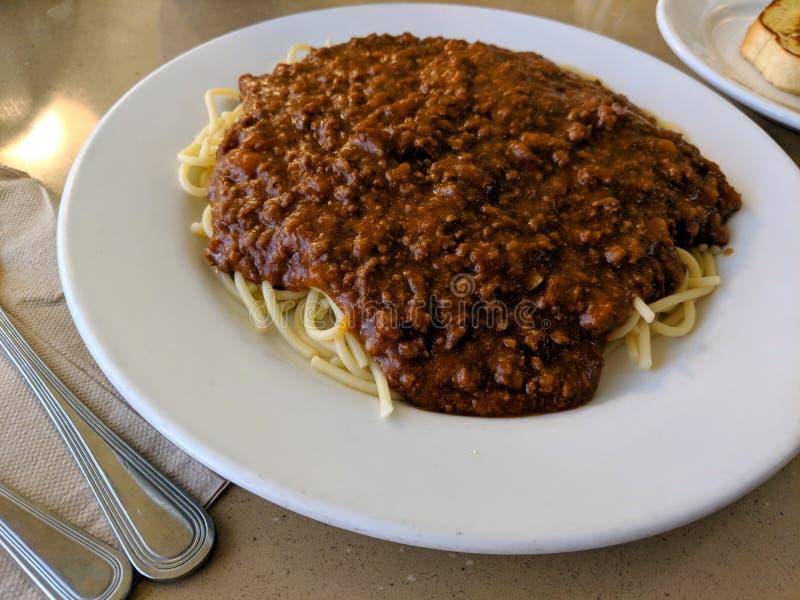 Les spaghetti plaquent avec 2 morceaux de pain à l'ail image stock
