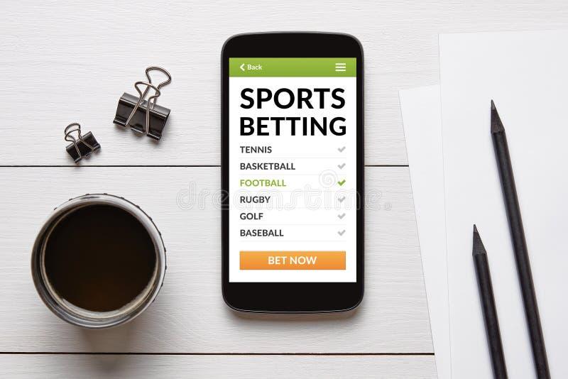 Les sports pariant le concept sur l'écran intelligent de téléphone avec le bureau objecte photos libres de droits