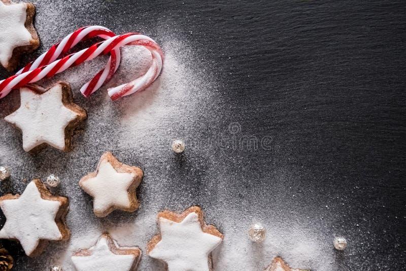 Les stars de la cannelle de Noël avec des cannes à sucre et du sucre en poudre sur fond sombre photos libres de droits