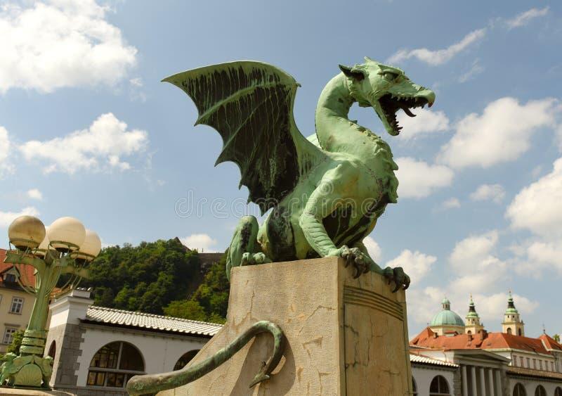 Les statues de dragon à Dragon Bridge et à la cathédrale de Saint-Nicolas au fond au centre de Ljubljana, Slovénie images libres de droits