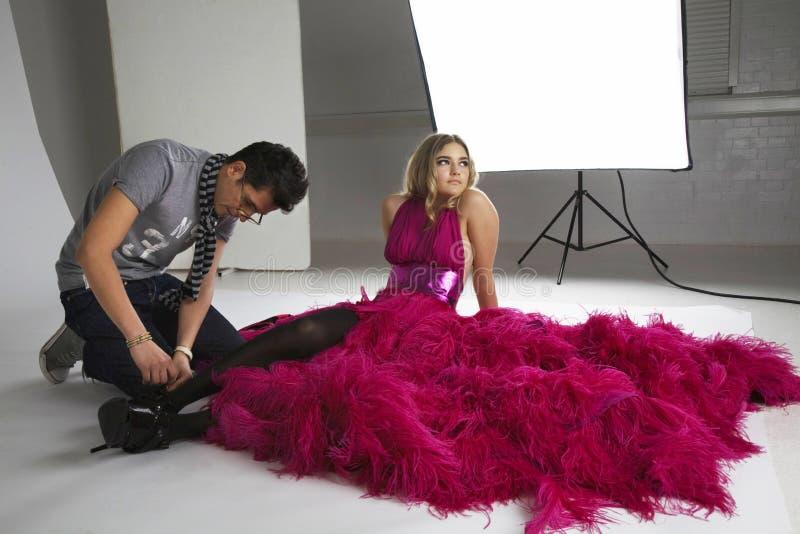 Les stylistes de mode ajuste les chaussures du modèle dans le studio photos libres de droits