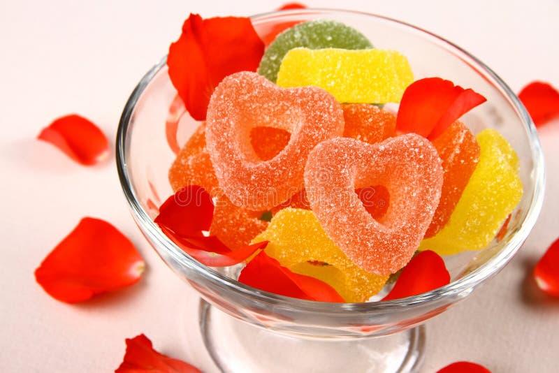 Les sucreries colorées de gelée dans la forme de coeur avec des fleurs part photos libres de droits