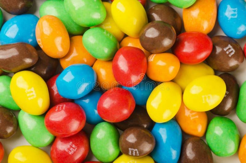 Les sucreries du ` s de M&M, se ferment d'une pile de sucrerie recouverte de chocolat colorée images stock