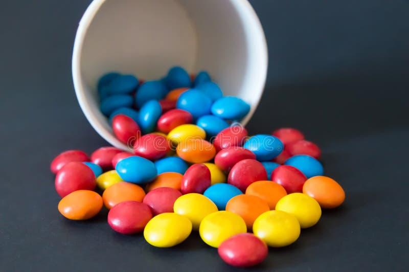 Les sucreries rondes multicolores de dragée ont versé d'une tasse de papier inversée sur un fond noir images stock