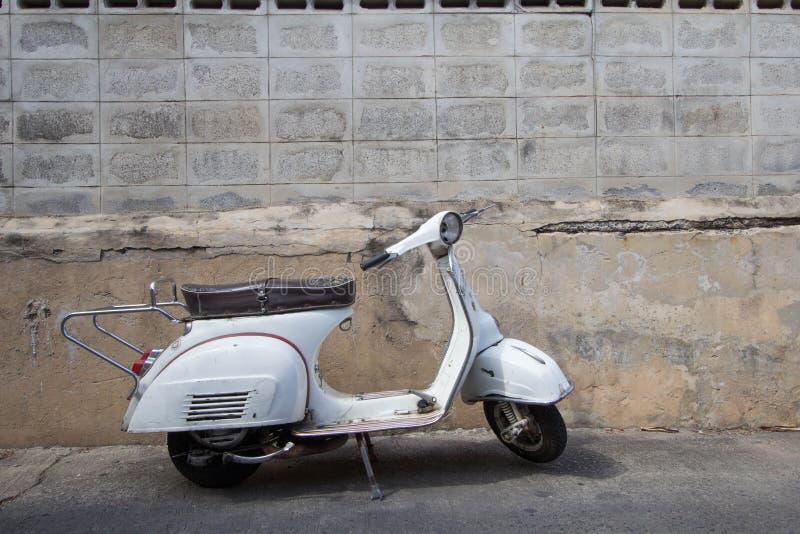 Les supports classiques blancs de scooter de Vespa se sont garés près du béton vieux images libres de droits