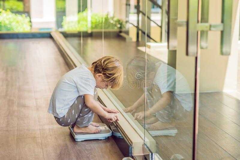 Les supports de garçon sur les échelles pour découvrir son poids photographie stock