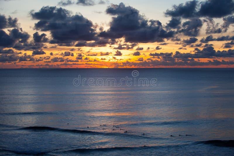 Les surfers attrapent les vagues de soirée dans l'océan photo stock