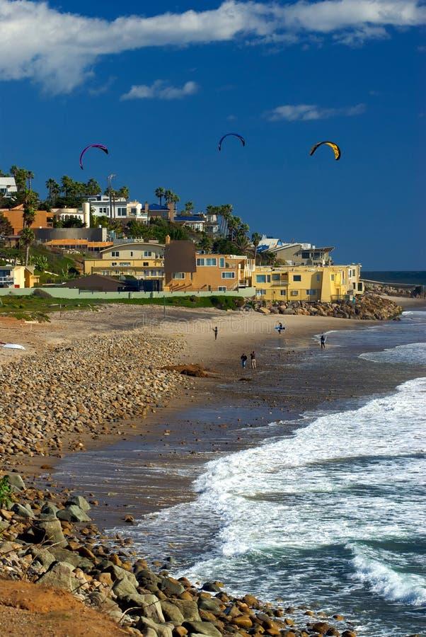 Les surfers de cerf-volant entrent dans l'eau le long du rivage rocheux photo libre de droits