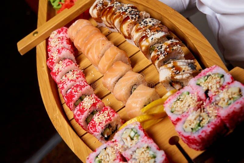 Les sushi ont placé sur un bateau en bois dans les mains du cuisinier photos libres de droits