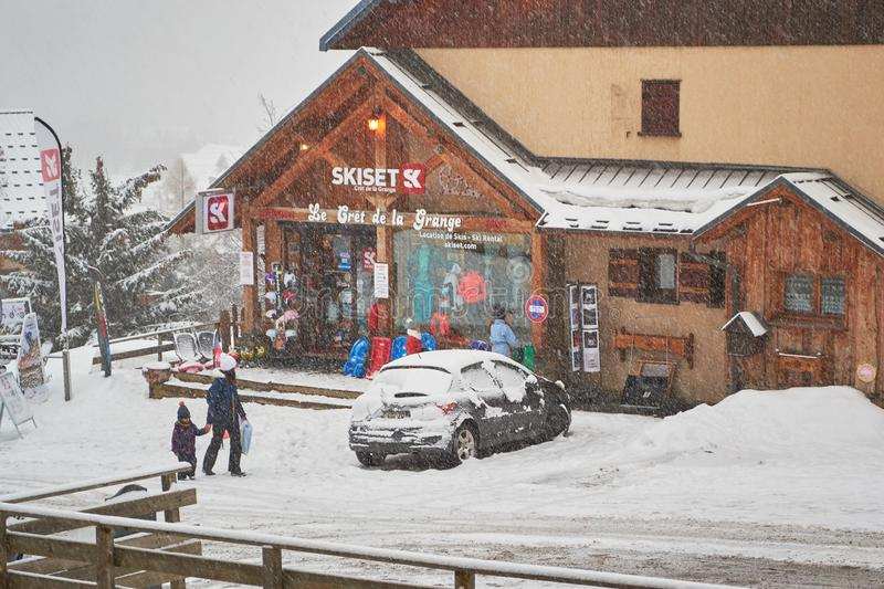 Skiset rental shop in Saint-Jean-d Arves village, Les Sybelles ski domain, during a snowy day, late Spring. Les Sybelles, France - March 14, 2019: Skiset rental royalty free stock image