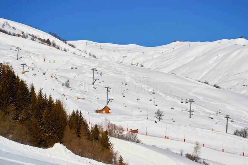 Les Sybelles ski domain in France - view of long chair lifts and pistes, on a blue sky day royalty free stock photography
