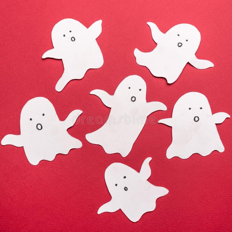 Les symboles traditionnels des fantômes pour haloween sur le fond rouge photo stock