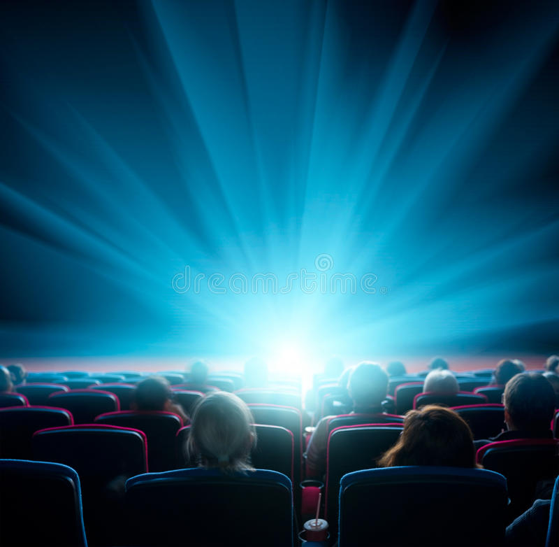 Les téléspectateurs observent la lumière brillante dans le cinéma photo stock