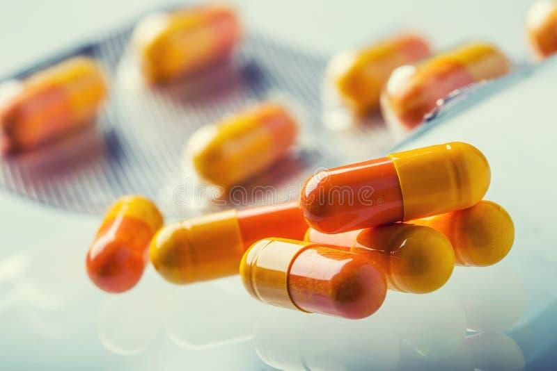 Les Tablettes de pilules capsulent ou médicament librement étendu sur le fond en verre photo libre de droits