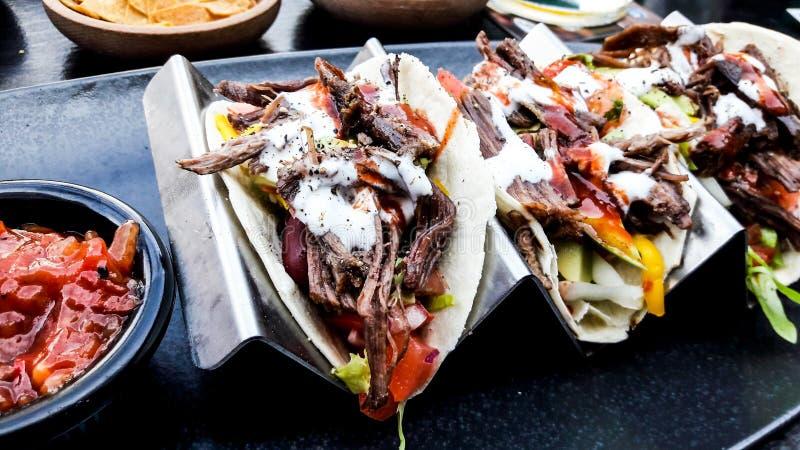 Les Tacos mexicains avec du boeuf et le Salsa/immersion sauce à la barre dehors photos libres de droits