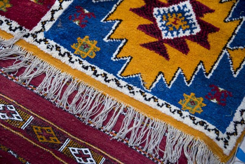Les tapis de berber tissés par main colorée ont écarté sur le plancher de bazar au Maroc photographie stock