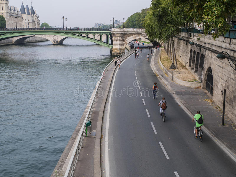 Les taqueurs et les bicyclettes succèdent la chaussée par la Seine sur Sunda photo libre de droits