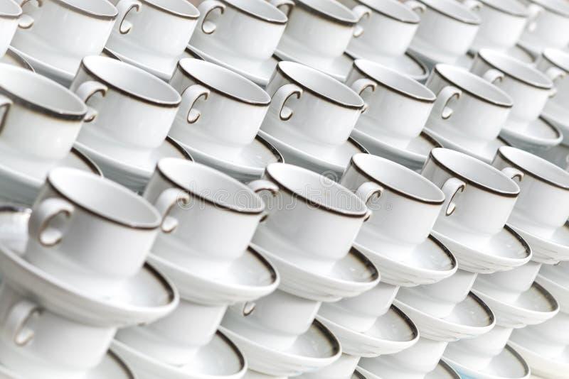 Les tasses de café avec des plats se tiennent empilées dans une rangée photos stock