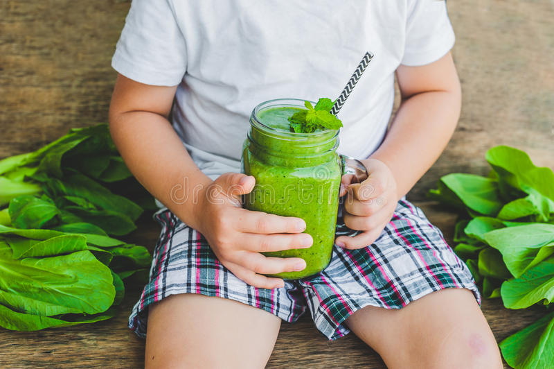 Les tasses de pot de maçon ont rempli de smoothie vert de santé de lait d'épinards, de banane et de noix de coco avec avec une cu image stock