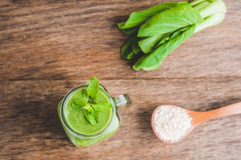 Les tasses de pot de maçon ont rempli de smoothie vert de santé de lait d'épinards, de banane et de noix de coco avec avec une cu photo stock