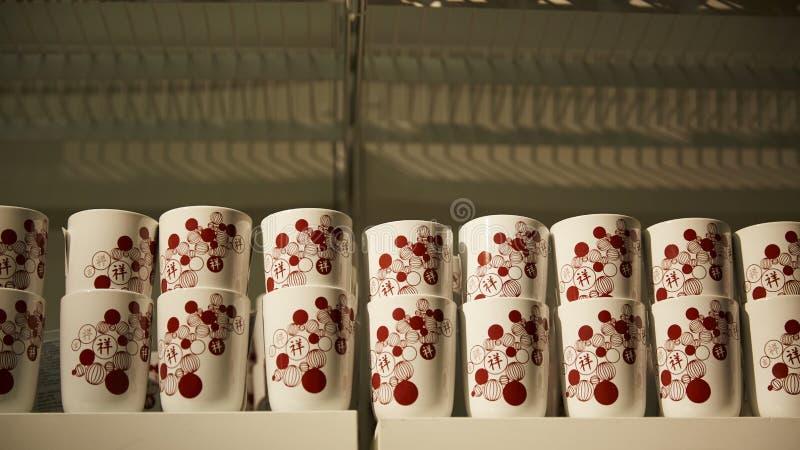 les tasses en céramique avec les caractères chinois à l'entreposage étire en vente photos stock