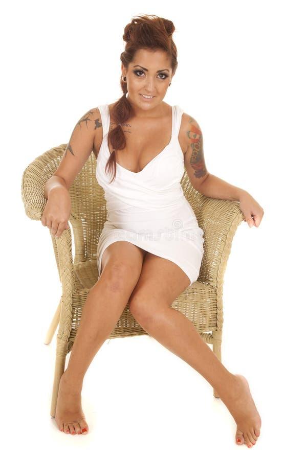 Les tatouages de femme reposent la chaise en osier faisant face au sourire photographie stock libre de droits