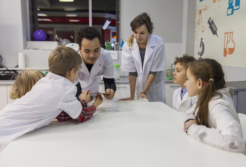 Les techniciens démontrent aux enfants l'expérience avec des classements en métal et un aimant images libres de droits