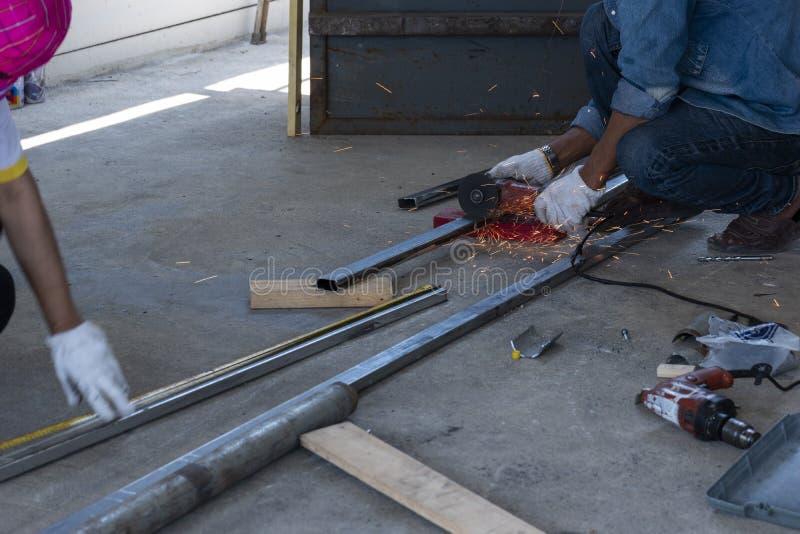 Les techniciens utilisent des machines de meulage pour couper des tuyaux d'acier photographie stock libre de droits