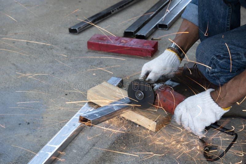 Les techniciens utilisent des machines de meulage pour couper des tuyaux d'acier photo libre de droits