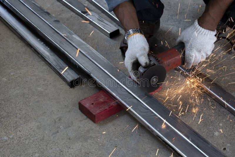 Les techniciens utilisent des machines de meulage pour couper des tuyaux d'acier photos libres de droits