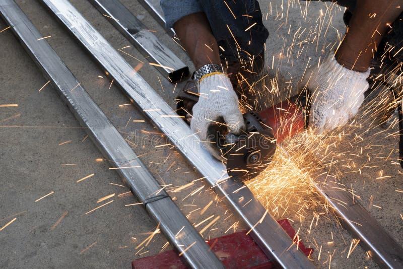 Les techniciens utilisent des machines de meulage pour couper des tuyaux d'acier images libres de droits