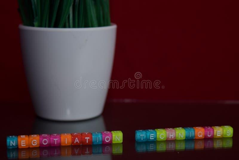 Les techniques de négociation textotent au bloc en bois coloré sur le fond rouge Bureau de bureau et concept d'éducation image stock