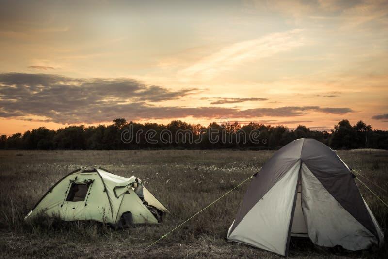 Les tentes de camping sur des campings sur la terre plate d'été mettent en place tout simplement et ciel dramatique de coucher du photo stock