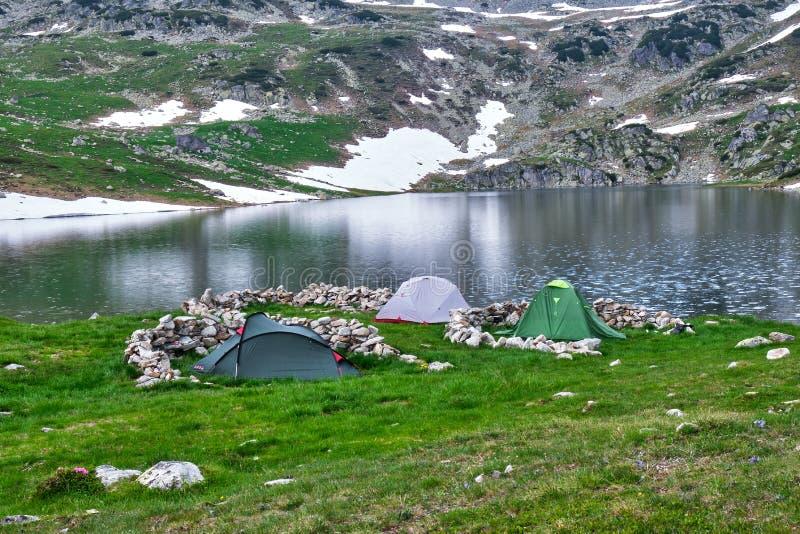 Les tentes ont lancé près du lac glaciaire Bucura, à la haute altitude, avec les piles en pierre autour de elles pour la protecti images libres de droits