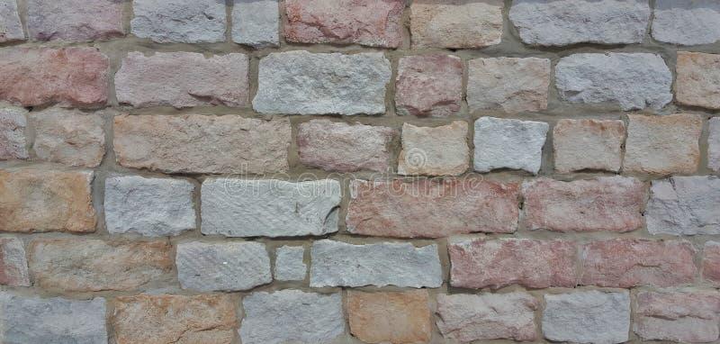 Les textures approximatives d'un mur de briques coloré photo stock