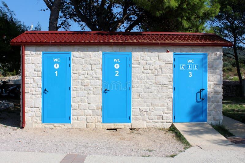 Les toilettes publiques extérieures de plage dans une rangée pour la femme des hommes et les personnes handicapées en nouvelle st image stock