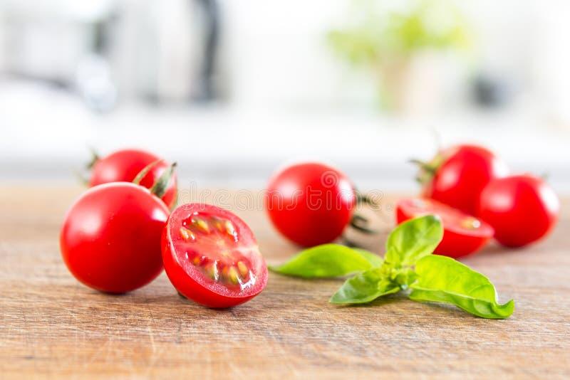 Les tomates-cerises lumineuses sur le conseil en bois et le blanc ont brouillé la cuisine moderne au fond photos libres de droits