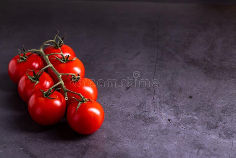 Les tomates-cerises sur des milieux de dalle en béton arrondissent photo libre de droits