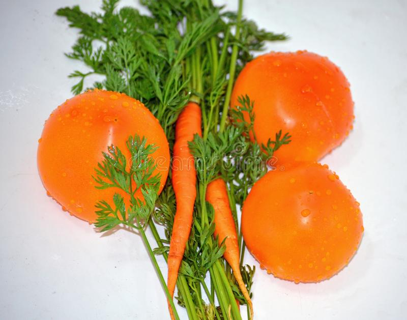 Les tomates et les carottes oranges juteuses mûres avec les feuilles vertes se trouvent sur une table blanche, vitamines naturell images libres de droits