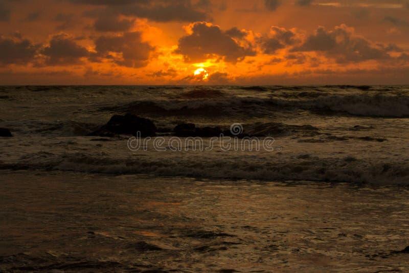 Les tonalités oranges du coucher du soleil se sont reflétées dans les vagues photographie stock libre de droits