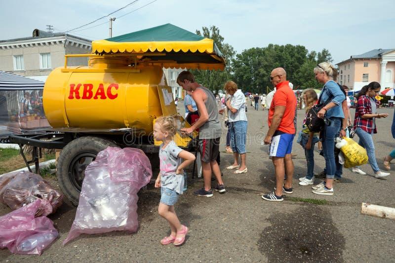Les touristes achètent le kvas sur la rue du village pendant la période du festival international annuel de la musique et des mét photographie stock libre de droits