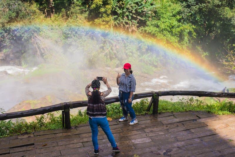 Les touristes apprécient l'arc-en-ciel de photographie dans la chute de l'eau photographie stock