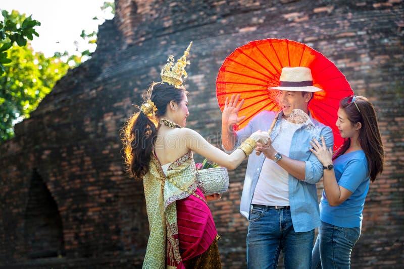 Les touristes apprécient le festival de Songkran Filles thaïlandaises et jeune homme caucasien éclaboussant l'eau pendant le fest images libres de droits