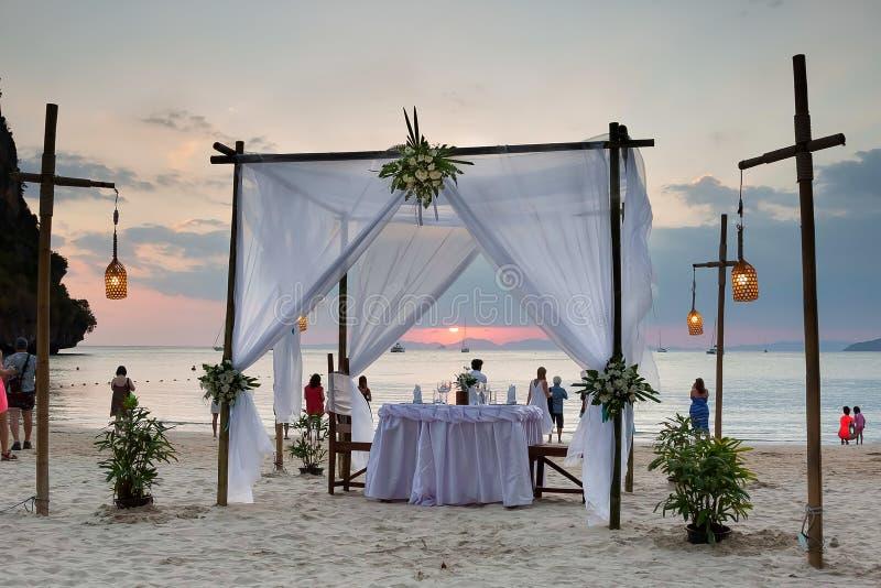 Les touristes appr?cient la vue de coucher du soleil sur la plage Sur la table d'ensemble de sable d?cor?e pour un d?ner romantiq images libres de droits