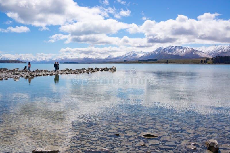 Les touristes asiatiques de la famille quatre photographiant le paysage et appréciant les eaux affilent photographie stock