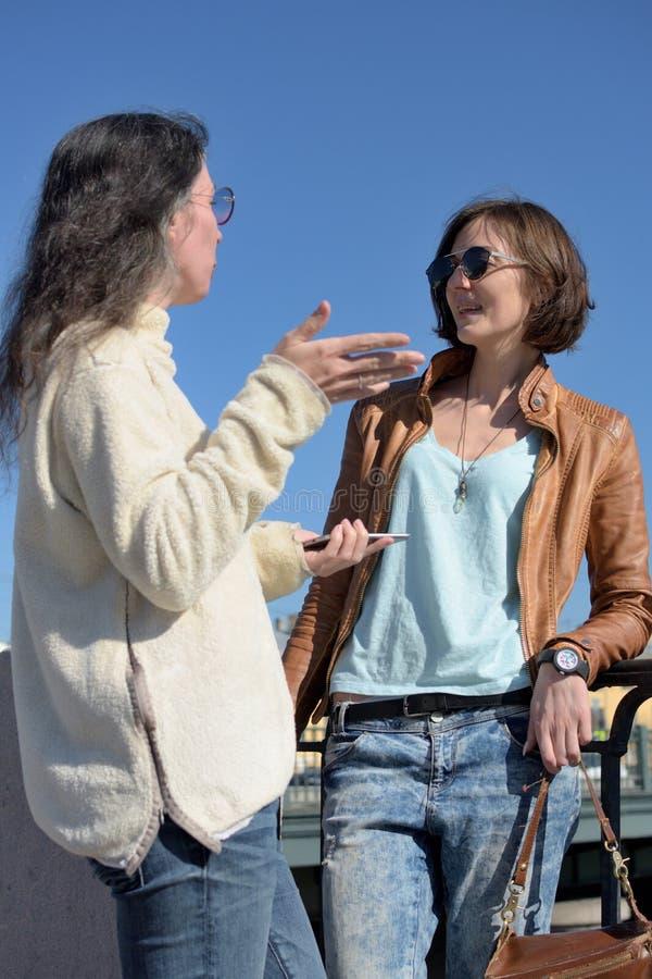 Les touristes de jeunes dames ont un arr?t ? un pont dans le St Petersbourg, Russie et discuter davantage de visite touristique image libre de droits