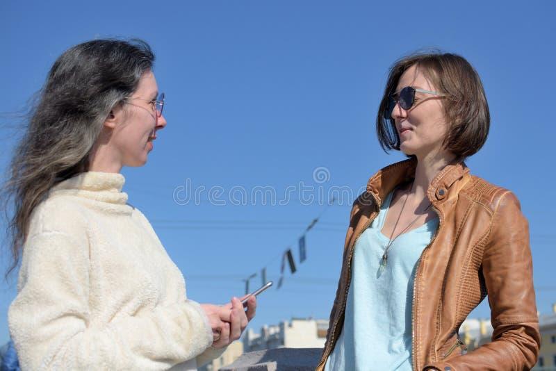 Les touristes de jeunes dames ont un arr?t ? un pont dans le St Petersbourg, Russie et discuter davantage de visite touristique photos stock