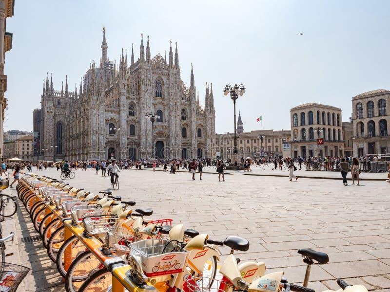 Les touristes de personnes marchent et montent des vélos dans un matin d'été chez Piazza del Duomo photos stock