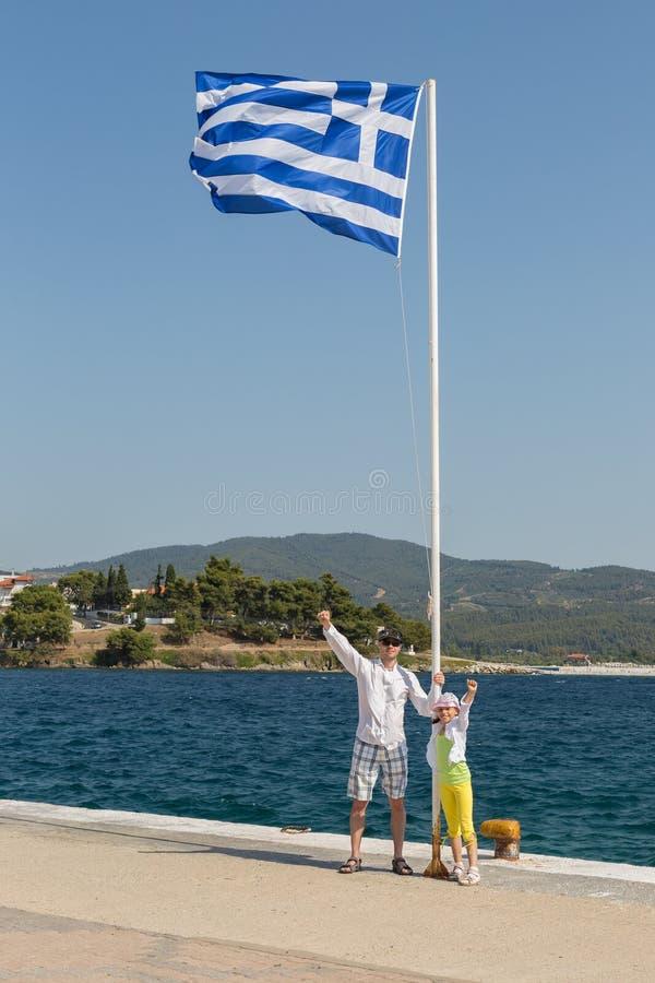 Les touristes engendrent et fille près du drapeau grec sur la côte égéenne de la péninsule de Sithonia photographie stock libre de droits